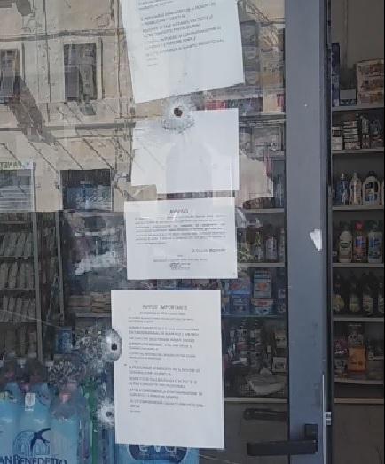 i fori dei colpi di proiettile sulla vetrina del minimarket